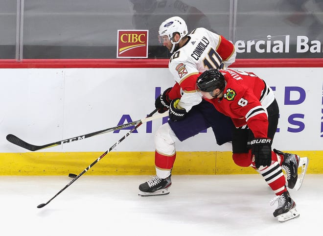 Dominik Kubalik (8) of the Chicago Blackhawks gets tangled up with Brett Connolly (10) of the Florida Panthers as they battle for the puck along the boards at the United Center on March 23 in Chicago. The Blackhawks defeated the Panthers 3-2.