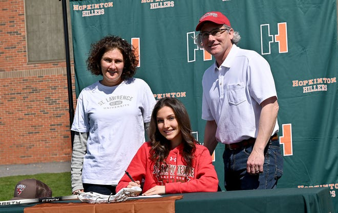 Hopkinton senior Lillian York signs a National Letter of Intent to play lacrosse at St. Lawrence, April 14, 2021. Behind her are her parents Ted and Heather York. York scored her 100th career goal in the Hillers' win on Monday