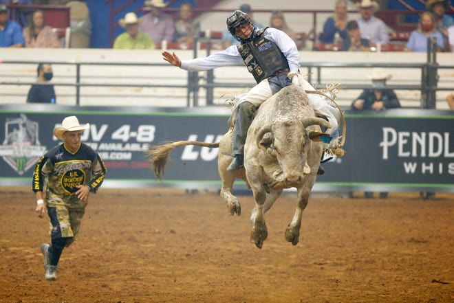 Bullfighter Frank Newsom of Paoli chases after Boudreaux Campbell who is riding Real Gun during Bullnanza at the Lazy E Arena in August.