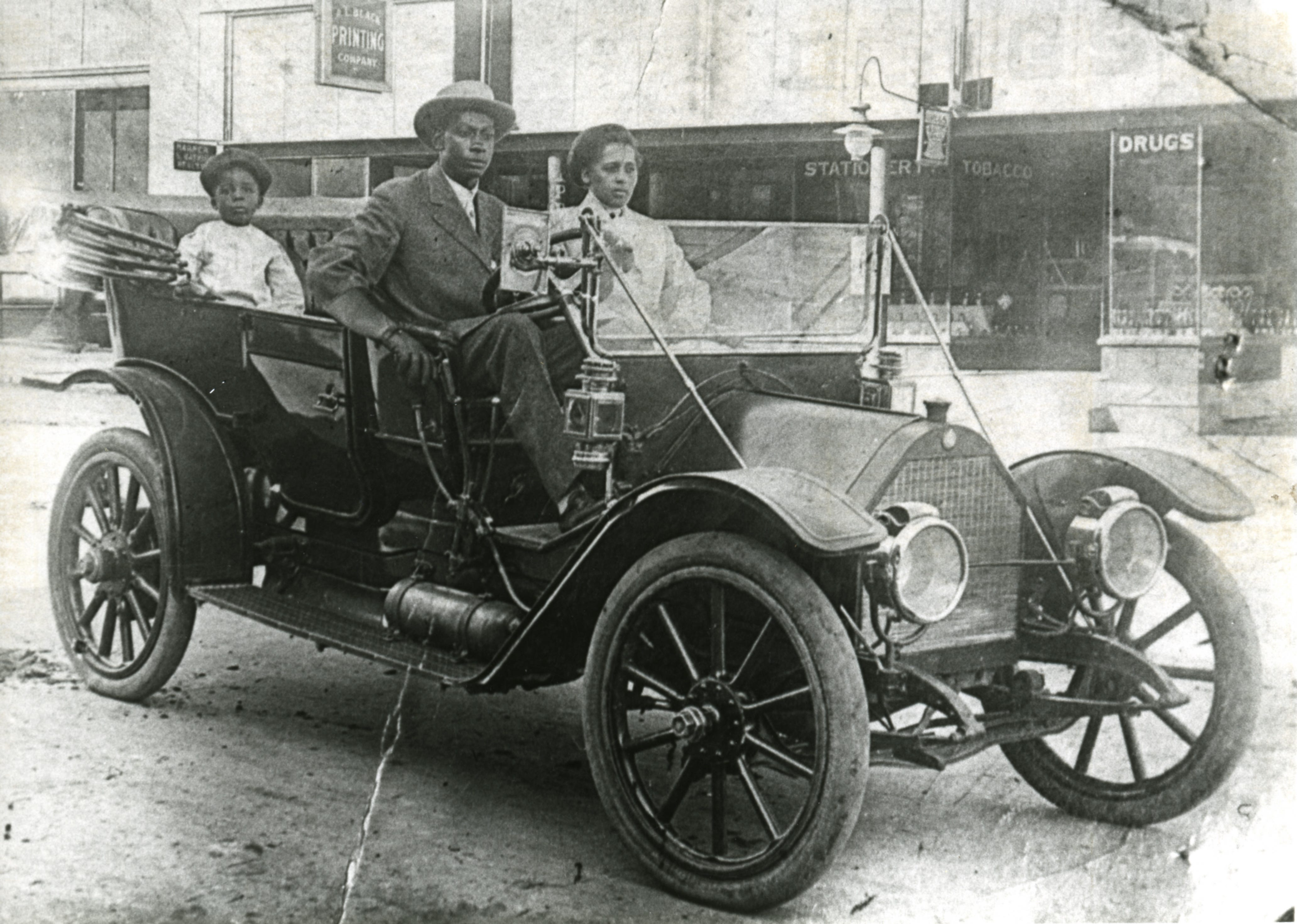 John Wesley Williams and wife, Loula Cotten Williams, and their son, William Danforth Williams, sitting in a 1911 Norwalk automobile. A sign advertising A.L. Black Printing Co., located at 114 S Boston Ave., Tulsa, is visible in the background. John was an engineer for Thompson Ice Cream Co. Loula was a teacher in Fisher. The Williams family owned the Dreamland Theatre, which opened in 1914 at 129 N Greenwood Ave., and was destroyed in the 1921 Tulsa Race Massacre.