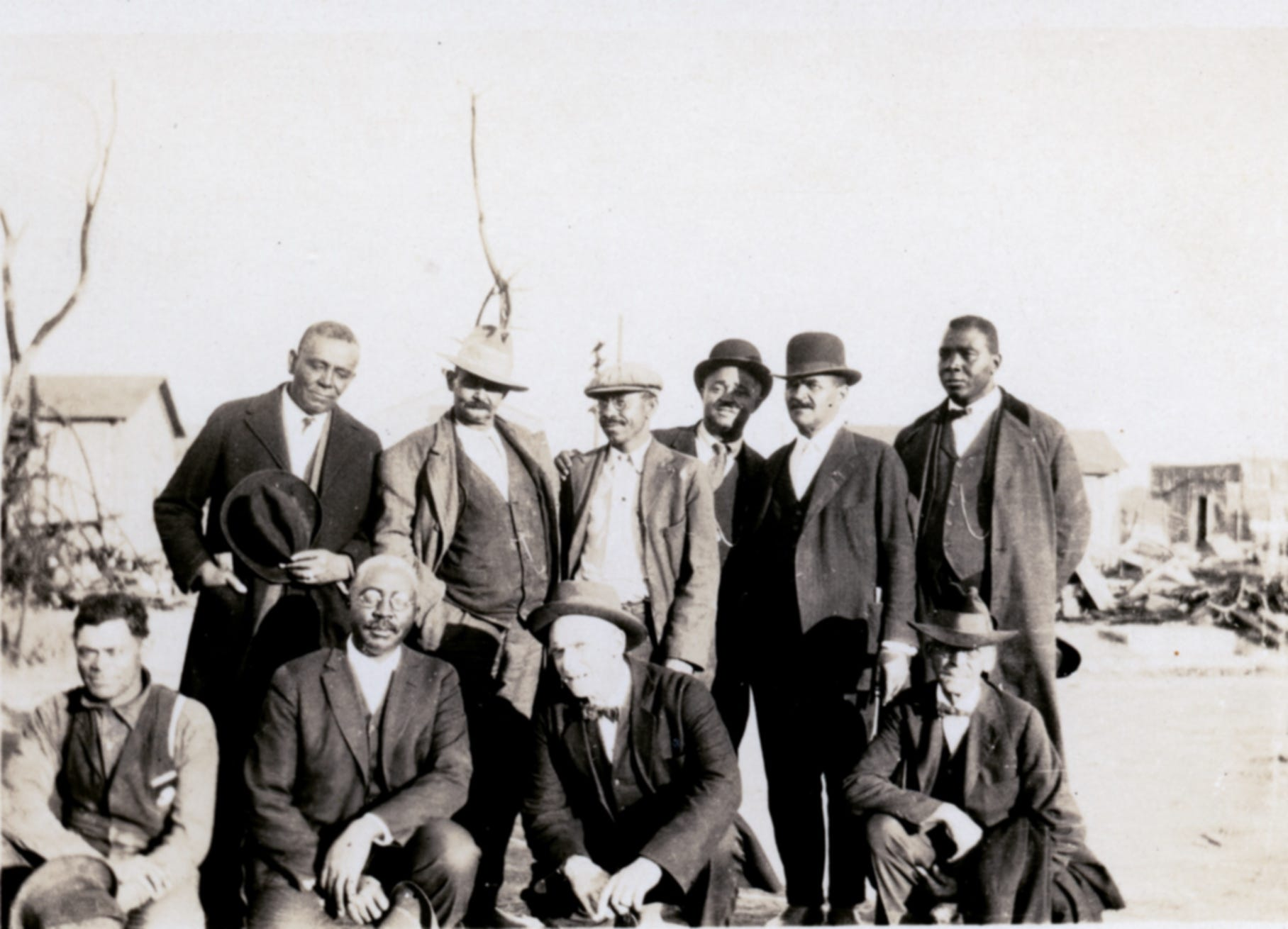 """The members of the Colored Citizens Relief Committee and East End Welfare Board following the 1921 Tulsa Race Massacre.  The individuals standing include (left to right) Williams, Phillips, Esta """"Essie"""" A. Loupe, Reverend E.N. Bryant, Horace T. Hughes and McLean. The men kneeling include (left to right) Perry Russell, O.W. Gurley, Bush, and Tucker Gilmer."""