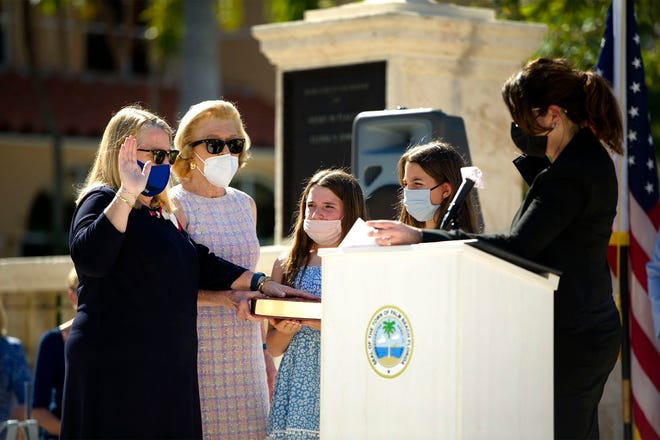Judge Lisa Small, right, swears in Danielle Moore, as mayor of Palm Beach, as her mother, former Palm Beach mayor Lesly S. Smith, and daughters Lesly Moore, 12, and Ali Moore, 11, watch at Memorial Fountain on Tuesday. MEGHAN McCARTHY/Palm Beach Daily News