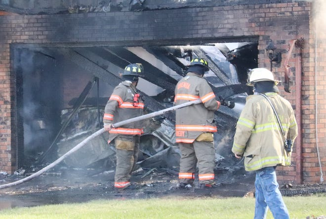 Chenoa firefighters pour water on flames inside the garage of the Richard Jacobs residence at 599 Mello Drive in Chenoa Wednesday morning. Neighbors reportedly heard an explosion before fire gutted the garage and home area. It was also said that any persons in the residence got out safely. No official information has been provided.