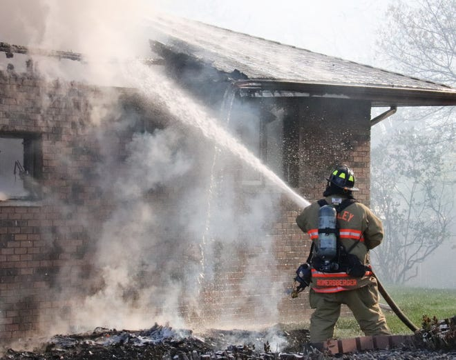 A member of the Gridley Fire Department shoots water on the garage of the residence at 599 Mello Dr. in Chenoa Wednesday morning. Besides Chenoa and Gridley, there were fire units from Fairbury, Lexington and Pontiac on hand to help with the blaze. There was no official report on the fire as of deadline.