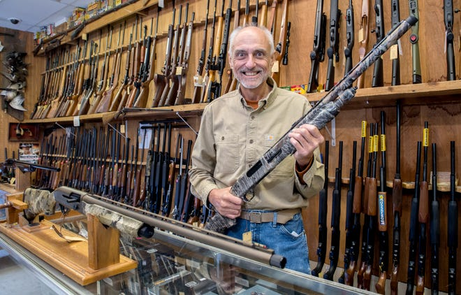 David Barth, owner of Pekin Gun and Sporting Goods, displays a pair of shotguns typically used for hunting turkeys and other wild game. Barth's business has been brimming with customers, and not just for the spring turkey season.