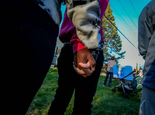 Kavon Sampson with Shannon Gibbons hold hands during the vigil Tuesday night in South Kingstown.