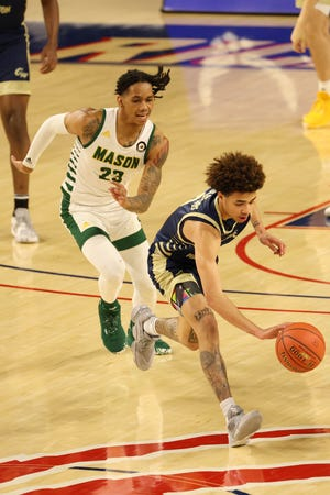 George Washington guard Tyler Brelsford chases a loose ball in front of George Mason guard Javon Greene during the second round of the Atlantic 10 Conference Tournament on March 4 n Richmond, Va. Brelsford has committed to Bryant.