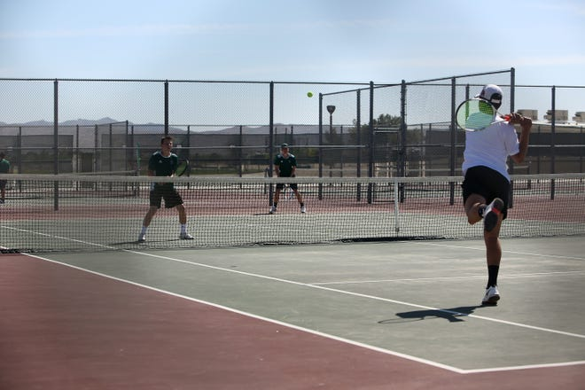 One of Oak Hills No.1 doubles players returns a serve from Burros' Ryan Cooper Monday afternoon.