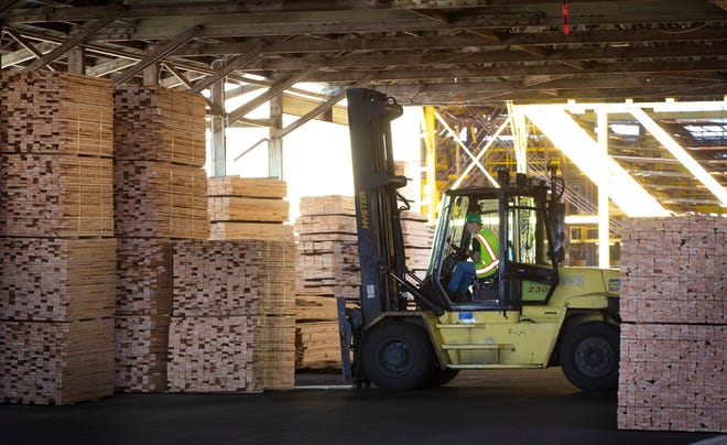 A worker moves lumber from a covered storage area for transport to market at Seneca Sawmill Co. in Eugene.