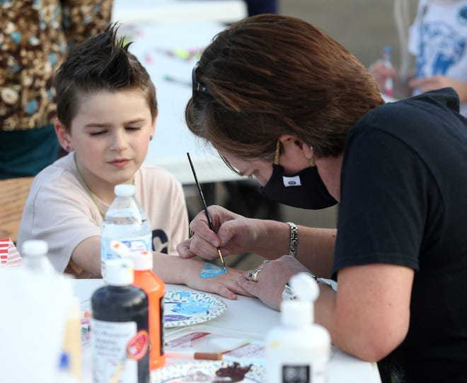 Lisa Galentine paints the hand of Alex Collier during the Leopards Unite Community Rally at Leopard Stadium. The event was held to generate support for the Louisville City School District's five-year, 5.9-mill emergency operating levy request that will appear on the May 4 election ballot.