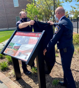 Police Chief Jeff Ledford and Fire Marshall Perry Davis unveil the new interactive sign at the Fallen Heroes Memorial in Shelby.