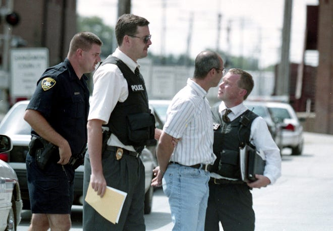 Mark Winger, second from right, is arrested by Springfield Police Officer Rodney Groth, Sgt. Doug Williamson and Detective Jim Graham in August of 2001. File/The State Journal-Register