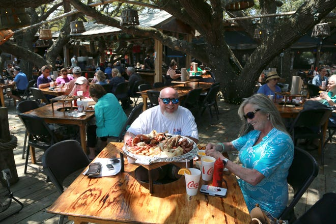 Shane Norryce and Debbie MacIlwinen of Greenville, South Carolina, enjoy lunch at The Crab Shack on Tybee Island. The Crab Shack has been struggling with staffing.
