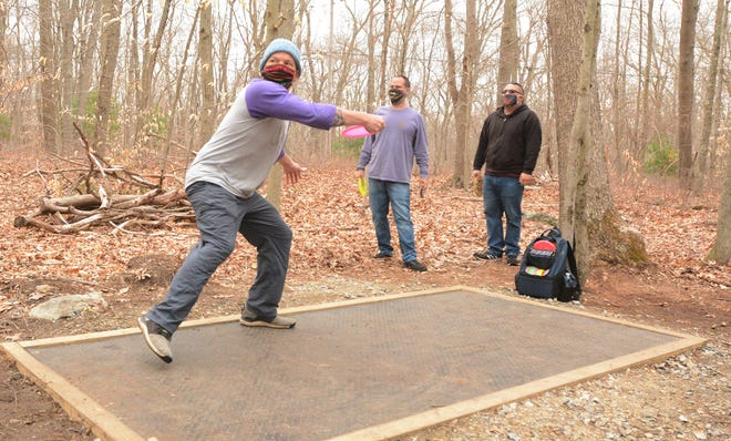 Josh Perry of Norwich throws his golf disc from the tee on the second hole Wednesday after a ribbon cutting ceremony for the nine hole Mohegan Park Disc Golf course in Norwich. At center Sean Tyler and Yoshinaka Mishima, both of Norwich, wait to throw. [John Shishmanian/ NorwichBulletin.com]