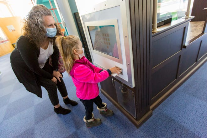Danielle Twemlow and her daughter Ramona, 5, play with a mock ATM on Wednesday morning at the Kansas Children's Discovery Center. Twemlow said Ramona could hardly sleep Tuesday night in anticipation of returning to the children's museum, which has been closed to the general public since March 13, 2020.