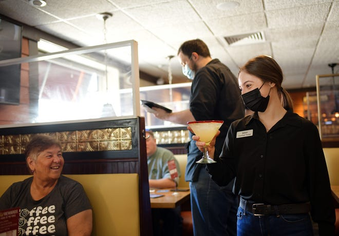 Server Sarah Passamonti delivers a drink to a table at the 99 Restaurant in Auburn on Wednesday.