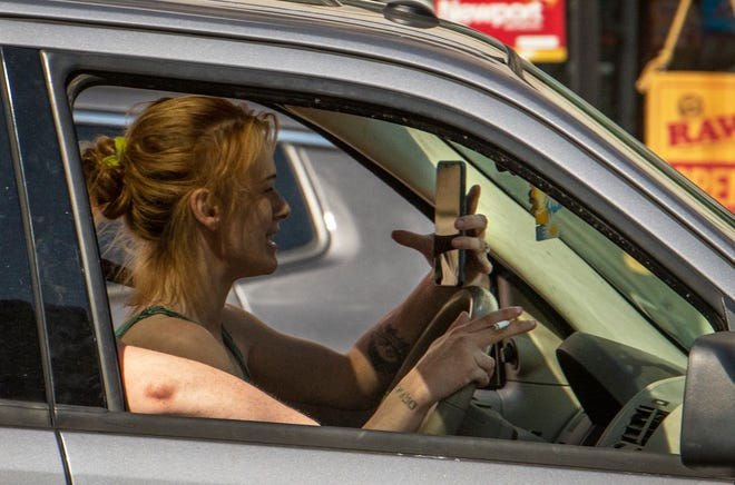 A driver travels on Front Street in Worcester with a cellphone in one hand and a cigarette in the other Wednesday.