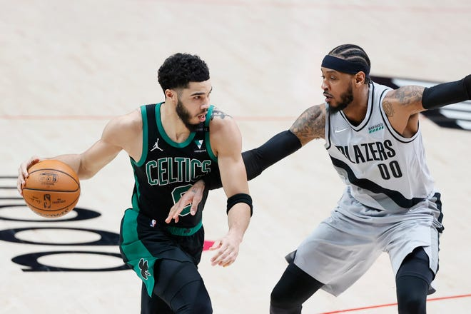 Celtics forward Jayson Tatum dribbles the ball while defended by Trail Blazers forward Carmelo Anthony during the second half Tuesday night in Portland, Oregon.