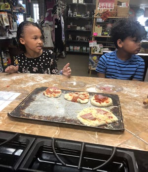 The children take turns shaping the dough and topping their own little pizzas during the Just for Kids cooking class.