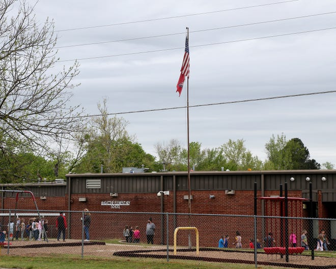 Children line up to return to the classroom after recess, Wednesday, April 14, at the Magazine Elementary School.