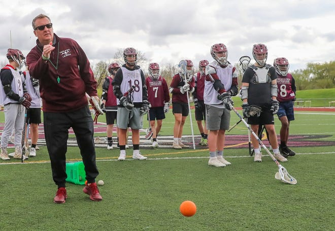 Canal Winchester boys lacrosse coach Victor Paini talks with players during practice April 12.