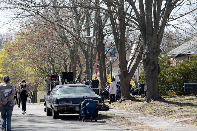 Members of the crew take a break and get on their phones in between filming of the Tender Bar at a home on Calvin Street in Braintree on Wednesday, April 14, 2021.