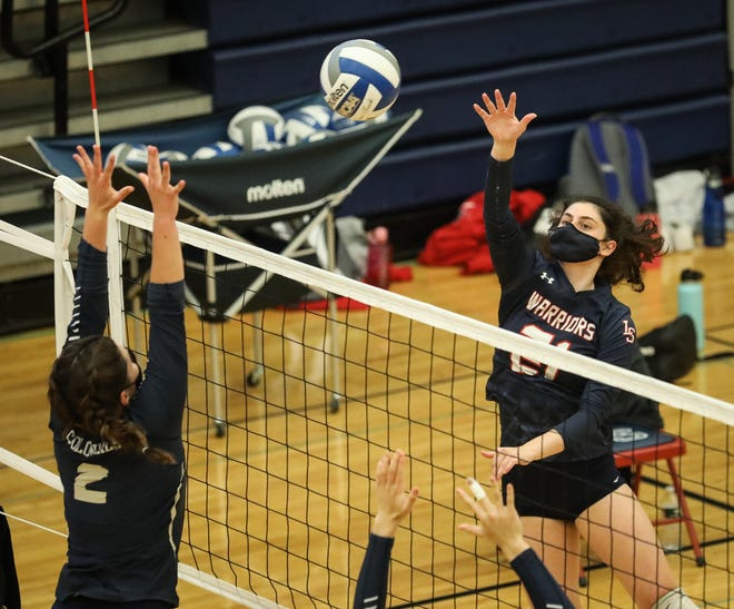 Lincoln-Sudbury senior Liz Lentino (21) hits the ball towards the net while being defended by Acton-Boxborough's Justine Amory (2) during the fourth set of a Dual County League semifinal championship game in Sudbury, April 13, 2021.
