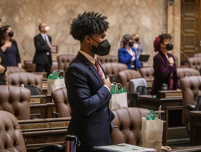 In this Jan. 11, 2021, file photo, Rep. Jesse Johnson, D-Federal Way, stands with other members at the beginning of the House session, where legislators were spaced at a social distance, in Olympia. Johnson hopes to see the Legislature end qualified immunity for police officers, which would allow them to be sued in state court, and to see it authorize community oversight boards that could have input on local policies and receive complaints about officers.