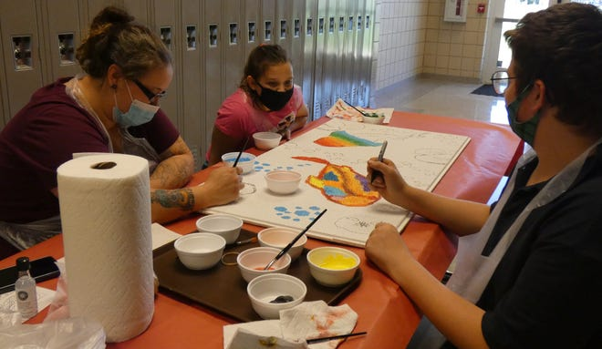 Shannon Ward, Lorelei Lugo and Jeffrey Ward, from left, work together on a colorful ceiling tileduring Family Art Night at Galion Middle School on Tuesday.