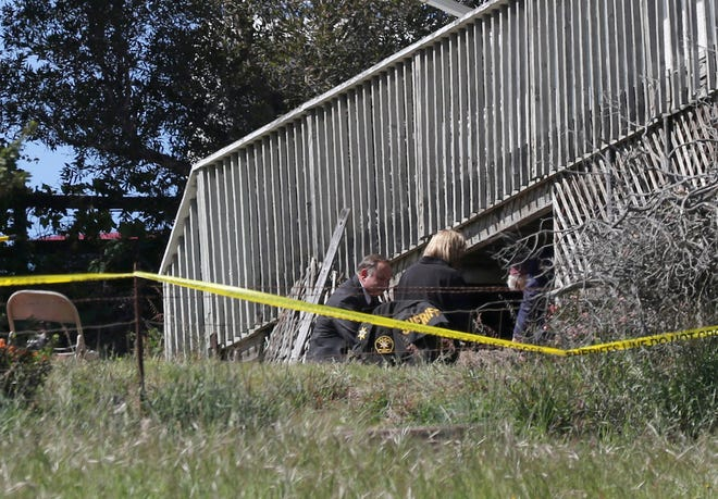 FILE - Pada file foto 16 Maret 2021 ini, personel Kantor Sheriff San Luis Obispo menggali di sebuah area di halaman belakang rumah Ruben Flores, di Arroyo Grande, California.