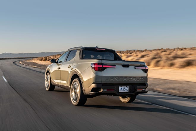 The 2022 Hyundai Santa Cruz has a smaller bed than competitor pickups. Signature T-taillights light up the rear.