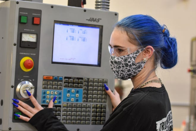 Girls like Kayla Garcia, with her bright blue hair and long fingernails, are redefining the look of an engineer. Here, she programs a CNC machine to cut a 6-inch ruler in the Engineering Technologies and Robotics lab.