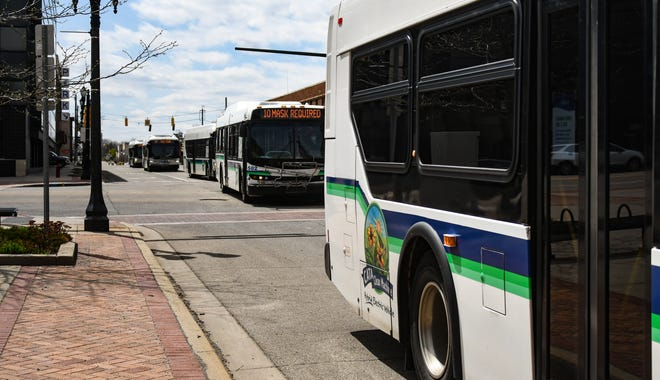 CATA buses cross East Michigan Avenue and Capital Avenue in downtown Lansing Wednesday, April 14, 2021.