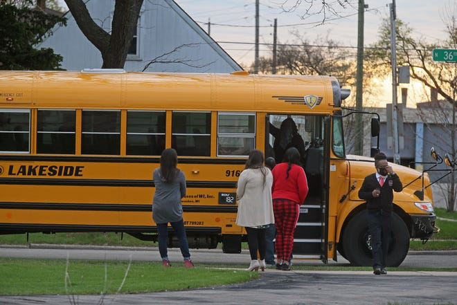 Principal Garry Lawson, right, walks toward Clemens School after getting off a school bus on the first day of his school's reopening on Wednesday.