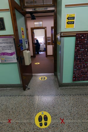 Social distancing markers can be seen on the floor in front of the main office at Fernwood Montessori School, 3239 S. Pennsylvania Ave., in Milwaukee for the school's reopening on Wednesday.