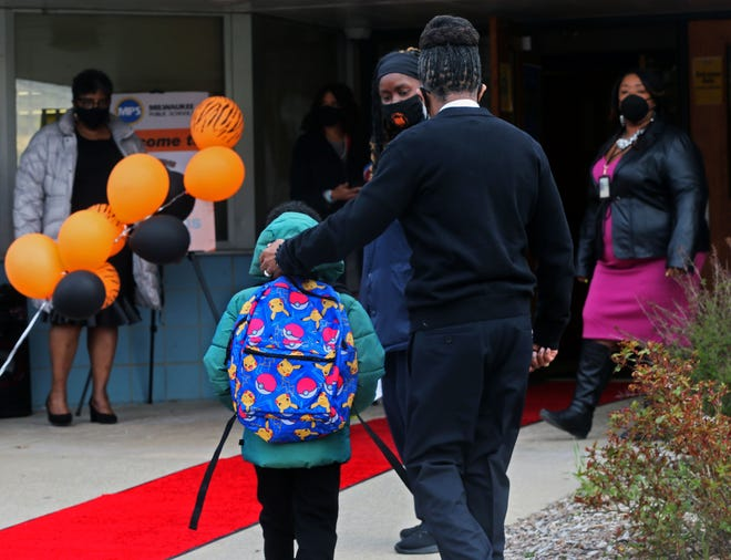 Principal Garry Lawson escorts a student who arrived for the reopening of Clemens School in April.