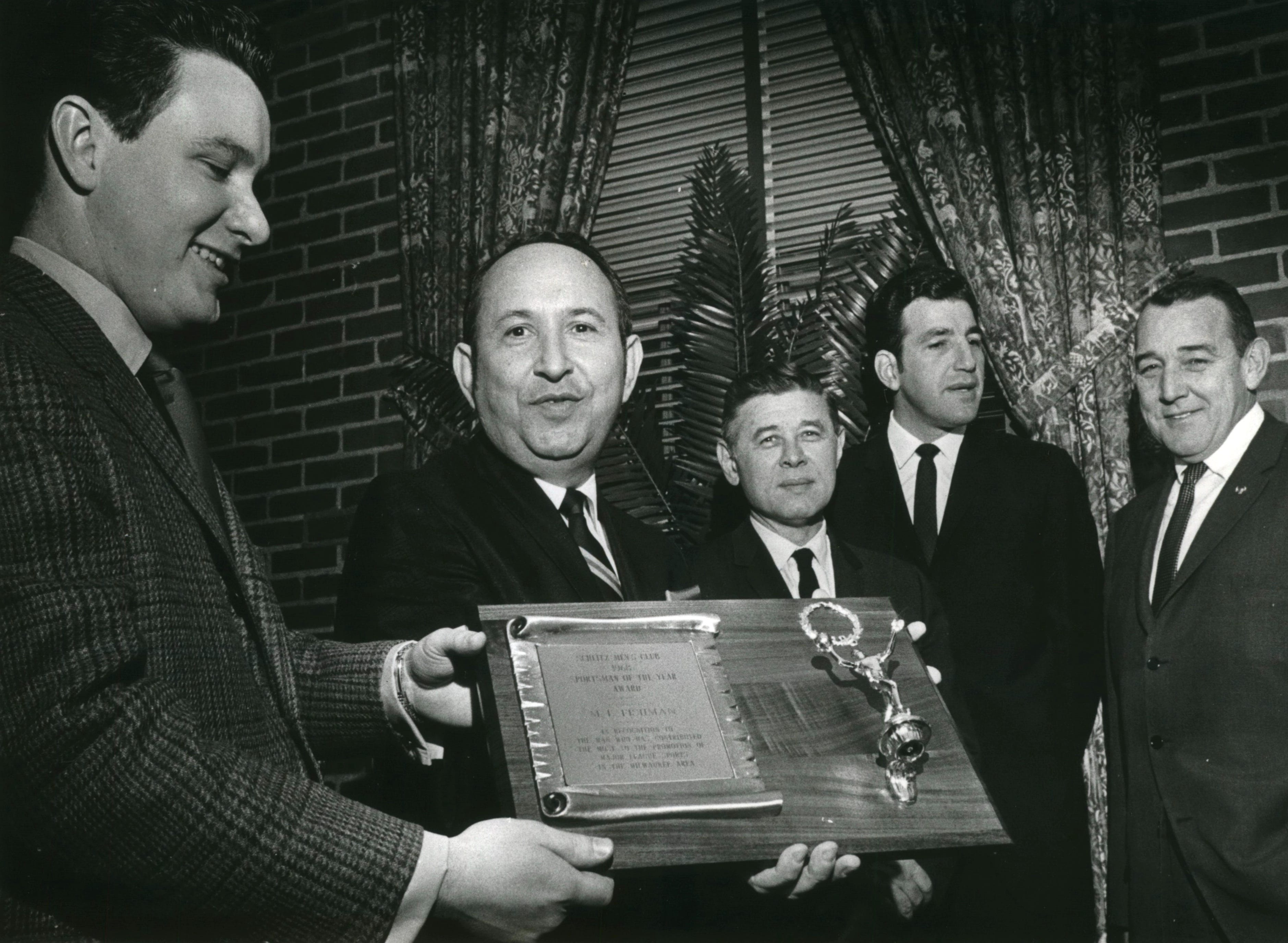 Marvin Fishman, second from left, is honored at the Schlitz clubhouse for his part in bringing professional basketball to Milwaukee.