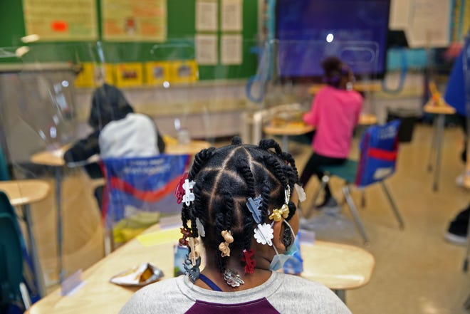 Students are separated by plexiglass shields in their classroom at Clemens School on Wednesday, the first day it is opened since the pandemic forced it to close.
