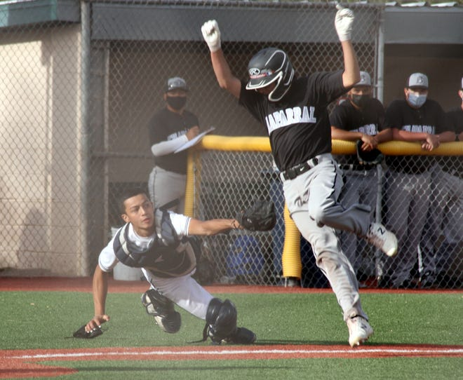 Wildcat catcher Ferno Milo lunges to apply the tag on a Chaparral base runner during Tuesday's double-header action at E.J. Hooten Park. The Chaparral base runner scored but the 'Cats went on to sweep the Lobos, 2-1 and 7-1.