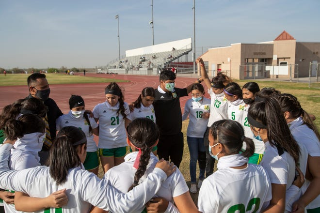 Coachella Valley varsity soccer players listen to their coach prior to the game against Desert Mirage in Thermal, Calif., on April 13, 2021.