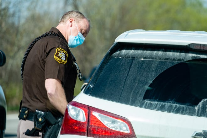 St. Clair County Sheriff Deputy David Wright conducts a traffic stop Wednesday, April 14, 2021, in Fort Gratiot.