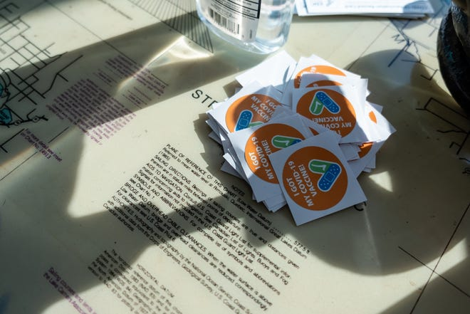 Vaccination stickers are piled on a table at the Great Lakes Maritime Center during a clinic Wednesday, April 14, 2021, in Port Huron.