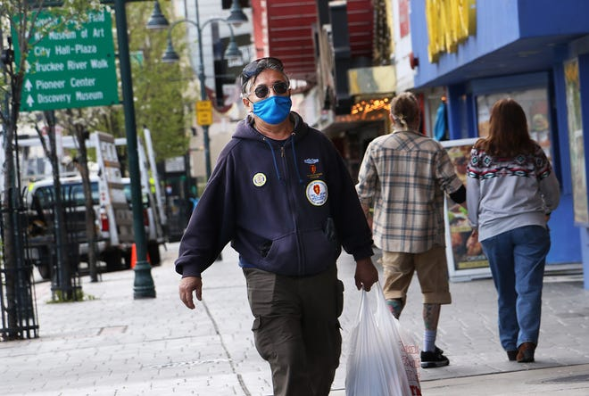 A man wearing a mask walks north on Virginia Street in downtown Reno on April 14, 2021.