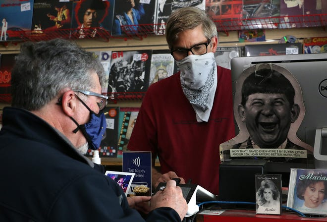 Recycled Records employee Joe Wilson, right, helps a customer while wearing a mask in Reno on April 14.