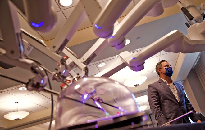 Gilbran Andujar, with Intuitive Surgical Inc., oversees the  work of a demo model of the da Vinci Xi Surgical System robot on a monitor (not seen) at the Shannon Women's and Children's Hospital on Tuesday, April 13, 2021.