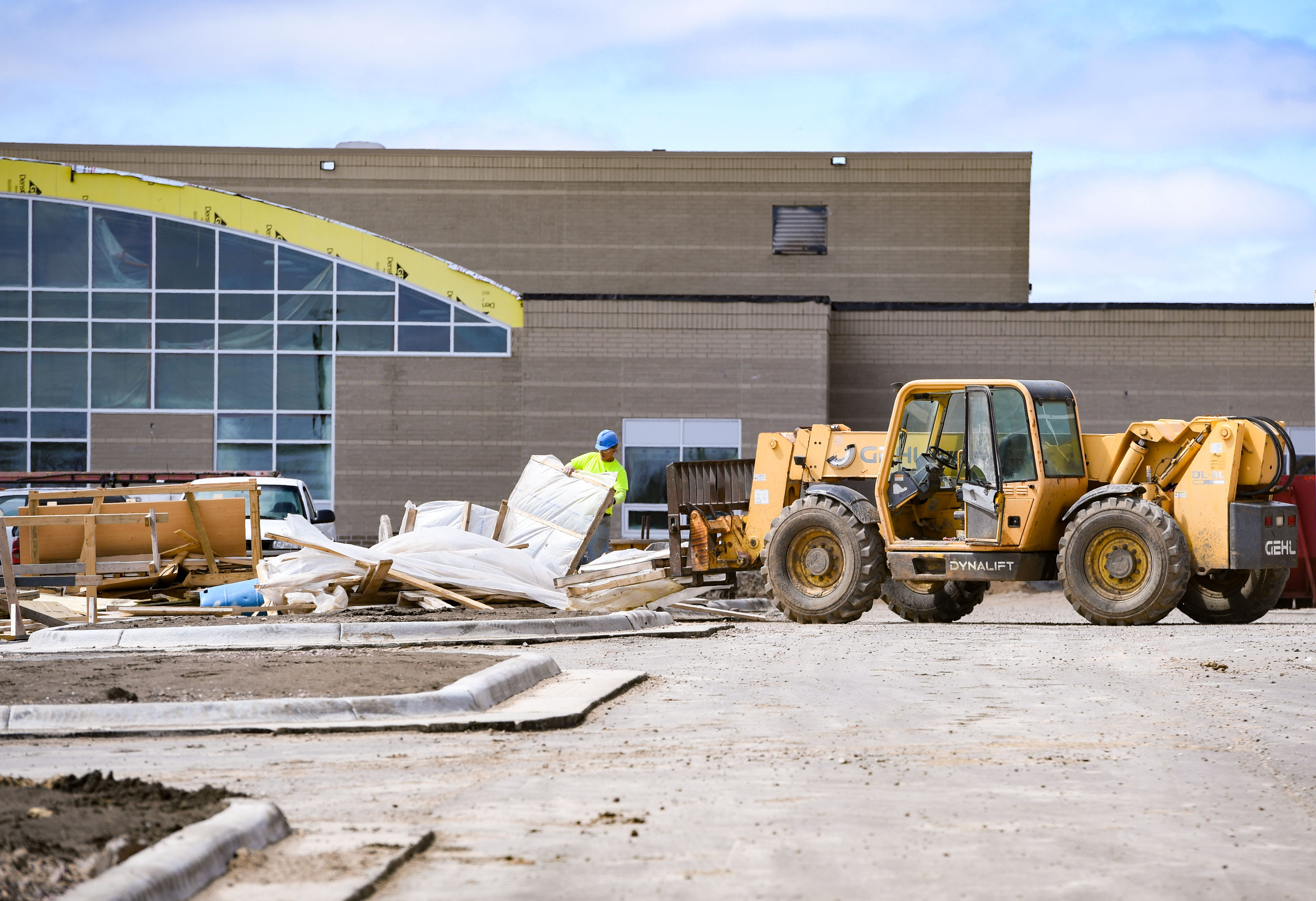 An exterior view of bulldozers in front of a school building