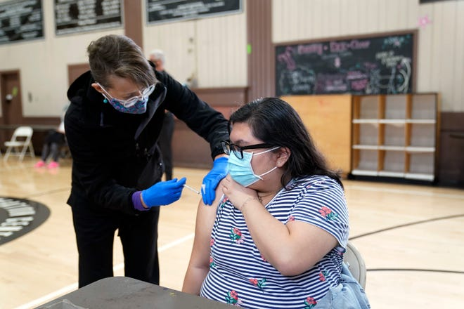 Esselen Reza (right) is pictured Tuesday receiving a dose of the Pfizer COVID-19 vaccine at the Banning Recreation Center in Wilmington, California. The site switched from its original plan to use the Johnson & Johnson COVID vaccine after federal drug safety regulators recommended that the U.S. pause use of the vaccine.