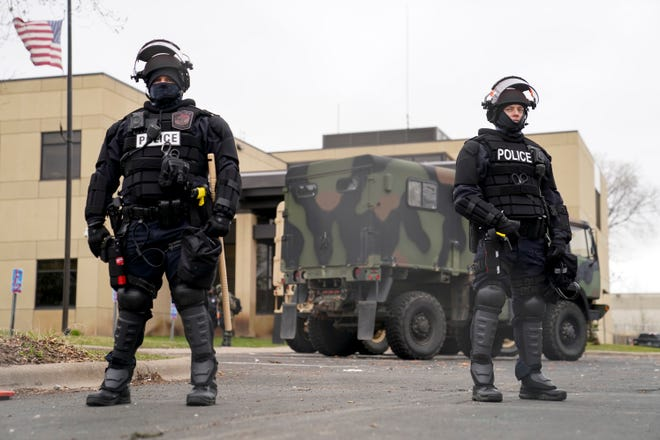 Police stand guard outside the Brooklyn Center Police Department on Tuesday amid the fatal shooting of Daunte Wright by a police officer in Brooklyn Center, Minnesota, over the weekend.