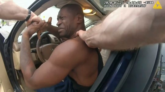 In this image from police body cam video, Minneapolis police officers attempt to remove George Floyd from a vehicle, on May 25, 2020, outside Cup Foods in Minneapolis, as it is shown Wednesday, March 31, 2021, during the trial of former Minneapolis police Officer Derek Chauvin in the case of Floyd's death, at the Hennepin County Courthouse in Minneapolis.