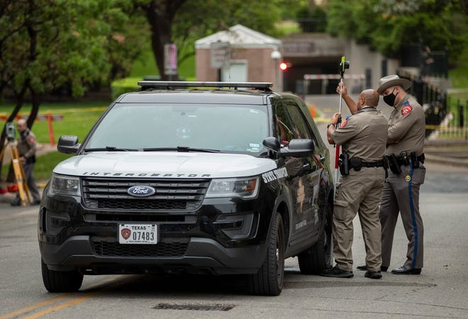 Texas Department of Public Safety troopers investigate the scene where a fellow trooper fatally struck a pedestrian lying in the intersection of 13th and Colorado streets early Thursday.